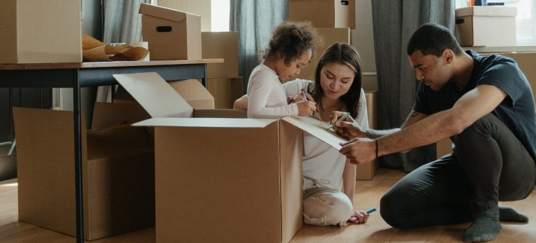 a couple with kid packing items, preparing for the relocation