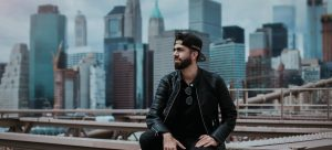 A man with beard, in black clothes and with a black basketball cap seating on a high place, with big buildings behind him, checking neighborhood before moving to his first apartment in Secaucus NJ