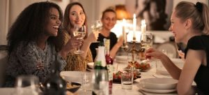 A lot women are sitting in a restaurant, eating and talking.